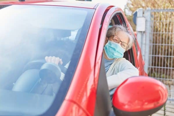 Senior driving with a mask for covid-19