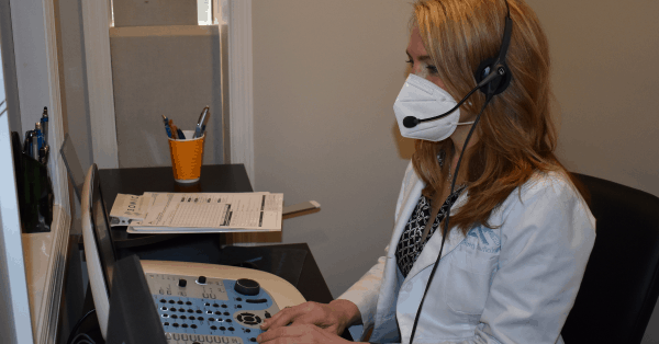 Dr. Ahlberg conducting hearing evaluation test