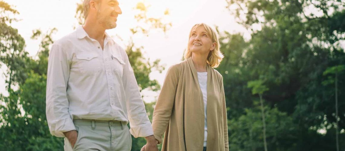 Senior active caucasian couple holding hands looks happy and carefree in the park in the afternoon autumn sunlight with copy space, happily retired spouse, elderly healthy lifestyle,happy anniversary.